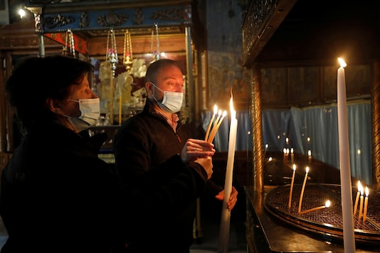 Visitors light candles in the Church of the Nativity, amid the coronavirus disease (COVID-19) outbreak, in Bethlehem in the Israeli-occupied West Bank. REUTERS/Mussa Qawasma