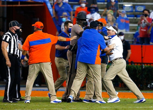 Florida coach Dan Mullen, right, is held back by coaches and law enforcement after a fight broke out at the end of the first half of the team's NCAA college football game against Missouri in Gainesville, Fla., Saturday, Oct. 31, 2020. (Brad McClenny/The Gainesville Sun via AP)