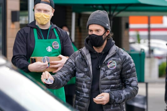 Former Seattle Sounders MLS soccer player Brad Evans, right, hands out stickers that read