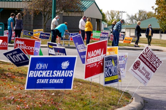 Voters wait in line to cast their ballot in the 2020 Presidential election during early voting in Noblesville, Ind.Wednesday, Oct. 14, 2020. (AP Photo/Michael Conroy, File)