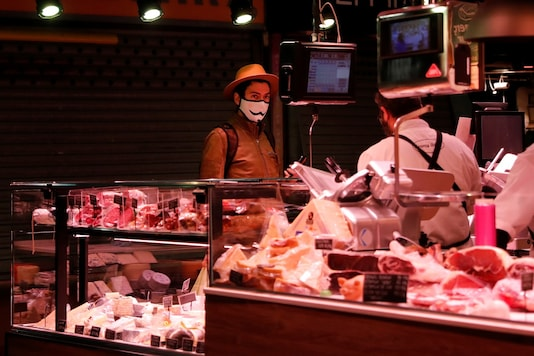 A man wearing a protective face mask buys meat at a market. (Credit: REUTERS)