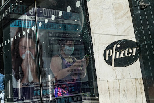 In this November 9, 2020, file photo, an ad for Covid-19 testing reflects on glass at a bus stop, as pedestrians walk past Pfizer world headquarters in New York. (AP Photo/Bebeto Matthews, File)