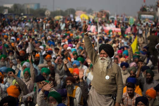 An elderly farmer shouts slogans as others listen to a speaker during a protest at the Delhi-Haryana border, on December 2, 2020. (AP Photo/Altaf Qadri)