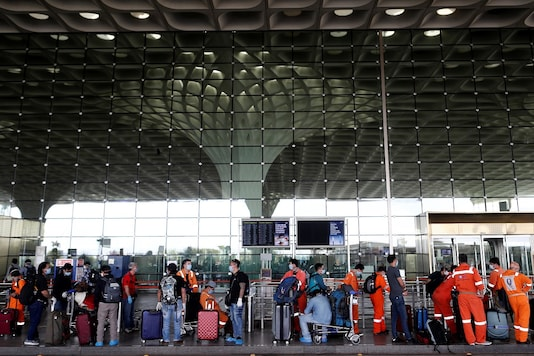 Passengers wearing protective face masks wait in a queue to enter Chhatrapati Shivaji International Airport. (REUTERS)