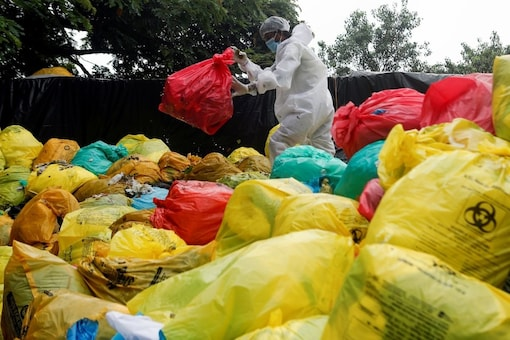 File photo of a man in PPE clears bags filled with medical waste at a Mumbai hospital amidst the spread of the coronavirus. (Image: Reuters)