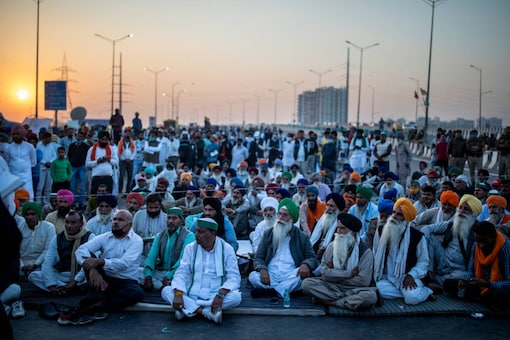 Farmers listen to a speaker in the middle of an expressway at the site of a protest against new farm laws at the Delhi-Uttar Pradesh border, on December 9, 2020. (AP Photo/Altaf Qadri)