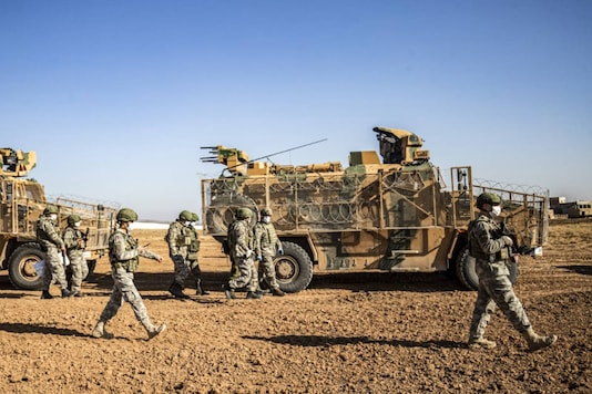 Turkish soldiers are pictured next to a military convoy during a joint Russian-Turkish patrol in Darbasiyah near the border with Turkey in Syria's northeastern Hasakah province on December 7, 2020. (Delil SOULEIMAN / AFP)