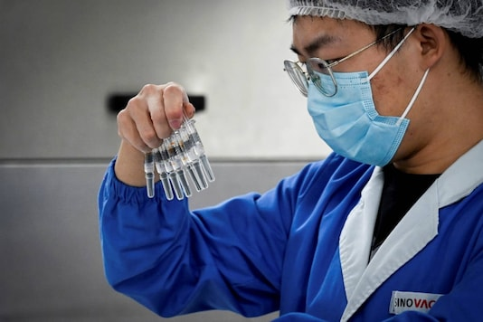 A staff member checking vaccines during a media tour of a new factory built to produce a Covid-19 vaccine at Sinovac, one of 11 Chinese companies approved to carry out clinical trials of potential coronavirus vaccines, in Beijing. (Photo by WANG Zhao / AFP)