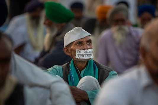 "A farmer's mouth is covered with a tape which reads, ""Walking on the footsteps of Gandhi, I am on hunger strike"", as farmers protesting against new agri laws block a major highway at the Delhi-Uttar Pradesh border, on December 9, 2020. (AP Photo/Altaf Qadri)"