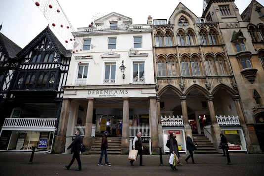 Shoppers walk past a Debenhams store, Browns of Chester, amid the outbreak of the COVID-19 in Chester, Britain. (REUTERS/Phil Noble)