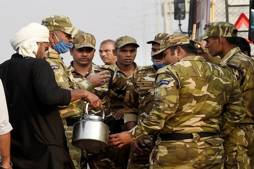 A farmer offers tea to security personnel during their 'Delhi Chalo' protest against new farm laws, at Delhi-Meerut Expressway in New Delhi. (PTI)