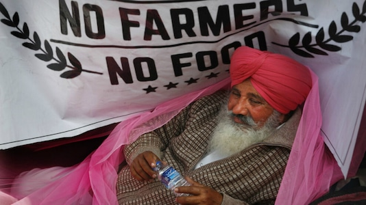 A farmer rests during the protest at the border. (AP)