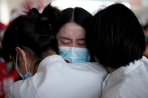 Medical workers hug at the Wuhan Tianhe International Airport after travel restrictions to leave Wuhan, the capital of Hubei province and China's epicentre of the novel coronavirus disease (COVID-19) outbreak, were lifted, April 8, 2020. REUTERS/Aly Song