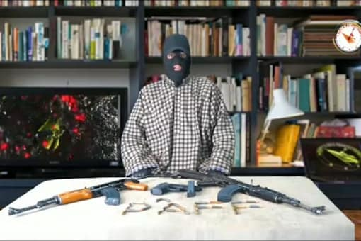 The man attired in a pheran spoke in Kashmiri. Two AK rifles and several rounds of ammunition were placed on a table in front of him while the background displayed a book shelf.