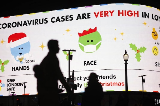 Pedestrians walk past a Covid-19 information display board warning people that 'Coronavirus cases are very high in London', in Piccadilly Circus, London on December 19, 2020. (Photo by Tolga Akmen / AFP)