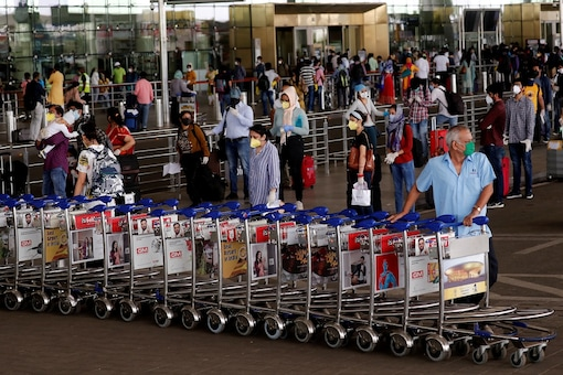 An airport staff member pushes trolleys at the entrance of Mumbai's airport. (REUTERS file photo)