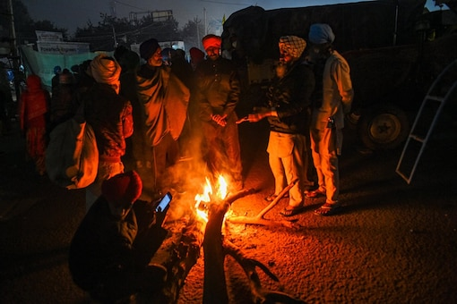 Farmers warm themselves near a bonfire during their ongoing protest against the farm laws in Delhi.