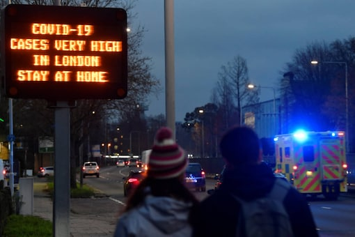 Pedestrians look on as an ambulance attending an emergency passes a public health warning sign, amidst the spread of the coronavirus pandemic, in London, on December 22, 2020. (REUTERS/Toby Melville)