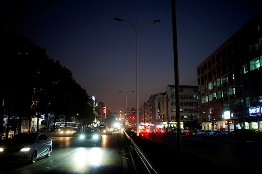 Cars drive on a street with the lighting system partially off in Yiwu, Zhejiang province, China.  REUTERS/Aly Song - RC2GTK9DOGW5