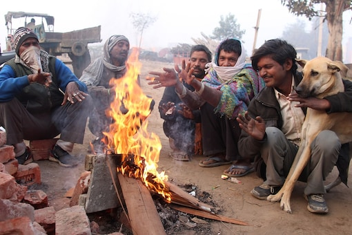 People sit around a bonfire to warm themselves during a cold and foggy morning in Gurugram. (PTI)