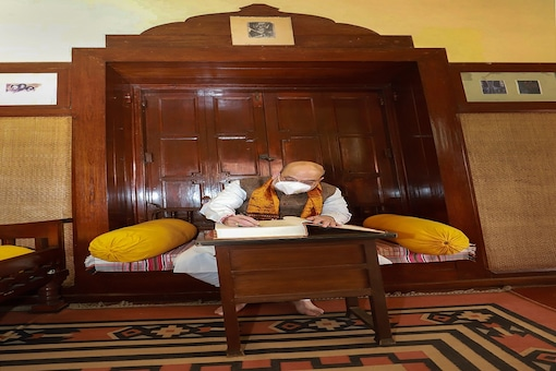 Home Minister Amit Shah signs the visitor's book during his visit to Rabindra Bhawan, at Shantiniketan in Birbhum district. (PTI)