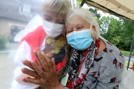 """Lily Hendrickx, 83, a resident at Belgian nursing home """"Le Jardin de Picardie"""" enjoys hugs and cuddles with Marie-Christine Desoer, the director of the residence, through a wall made with plastic sheets to protect against potential coronavirus disease (COVID-19) infection, in Peruwelz, Belgium, July 1, 2020. REUTERS/Yves Herman"""