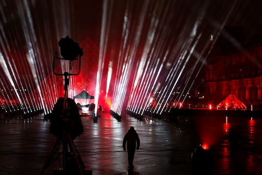 """A technician walks in the courtyard of the Louvre museum during the rehearsal of a show by French DJ David Guetta, in Paris, Tuesday, Dec. 29, 2020. Superstar DJ David Guetta has, quite literally, been brought back to Earth by the coronavirus pandemic and says his music has benefitted as a result. Back in his native Paris to record a New Year's Eve show, the composer of ear-worm dance hits said he has produced """"tons of new music"""" while hunkering down from the virus.(AP Photo/Thibault Camus)"""