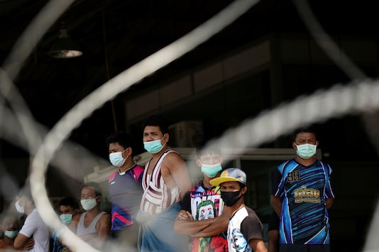 FILE PHOTO: Migrant workers stand in front of a closed shrimp market, amid the coronavirus disease (COVID-19) outbreak, in Samut Sakhon province, in Thailand, December 20, 2020. REUTERS/Athit Perawongmetha/File Photo