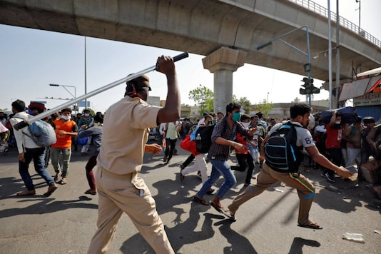 A policeman wields his baton to disperse migrant workers who were demanding train service to their home state of Bihar, after a limited reopening of India's giant rail network following a nearly seven-week lockdown to slow the spread of Covid-19), in Ahmedabad on May 17, 2020. (REUTERS/Amit Dave)