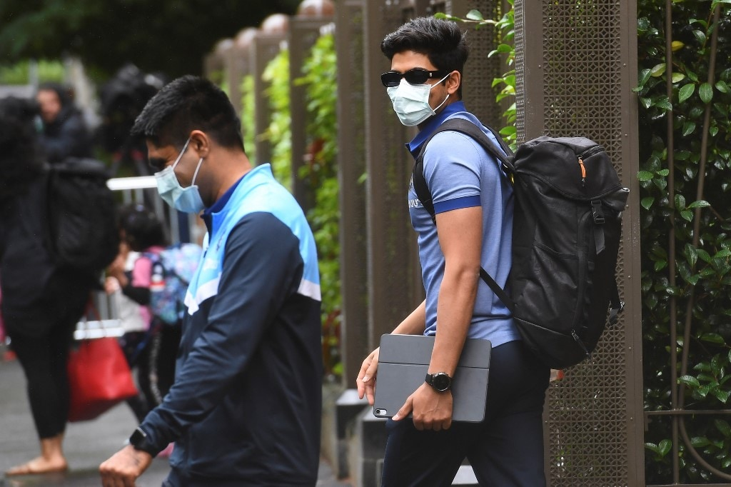 India's Shubman Gill (R) leaves the team's hotel in Melbourne on January 4, 2021, as the Australian and Indian cricket teams relocate to Sydney for the third cricket Test on January 7. (Photo by William WEST / AFP)