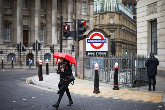 A woman holding umbrella crosses a street at the Bank Junction, amid the coronavirus disease (COVID-19) outbreak, in London, Britain, January 5, 2021. (Image: Reuters)