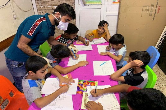 Iraqi orphan children draw in the classroom of an orphanage house during a curfew imposed to prevent the spread of the coronavirus disease (COVID-19), in Baghdad, Iraq. (Reuters)
