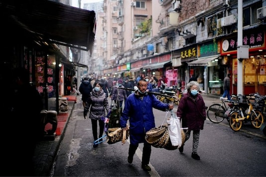 People wearing protective masks walk at a street market almost a year after the start of the coronavirus disease (COVID-19) outbreak, in Wuhan, China. (Reuters)