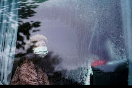 A woman wearing face mask looks out from a bus almost a year after the global outbreak of the coronavirus disease (COVID-19) in Wuhan, Hubei province, China December 7, 2020. Picture taken December 7, 2020. REUTERS/Aly Song
