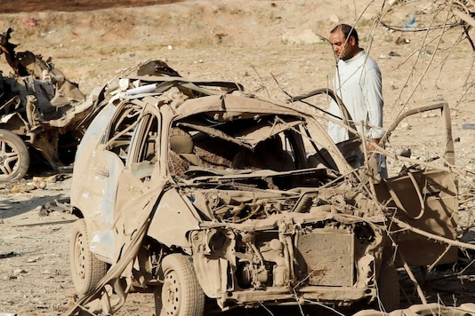 FILE PHOTO: An Afghan man inspects the wreckage of a car at the site of a truck bomb blast in Ghani Khel district of Nangarhar province, Afghanistan, October 3, 2020.REUTERS/Parwiz/File Photo