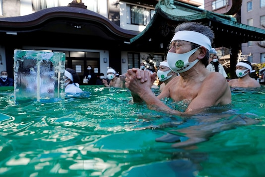 Participants wearing protective face masks amid the coronavirus disease (COVID-19) outbreak, pray as they take an ice-cold bath during a ceremony to purify their souls and to wish for overcoming the pandemic at the Teppozu Inari shrine in Tokyo, Japan, January 10, 2021. REUTERS/Kim Kyung-Hoon