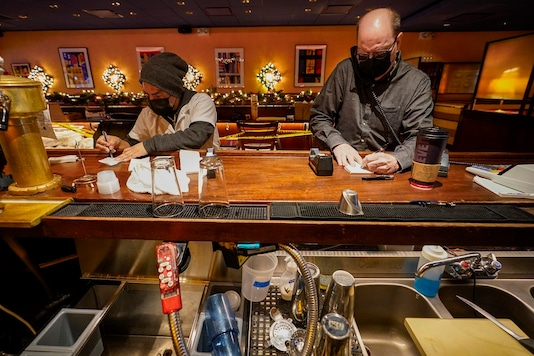 Steve Olsen, right, owner of the West Bank Café and Segundo Agueza take to-go orders over the phone in the empty restaurant, Saturday. (AP Photo/Mary Altaffer)