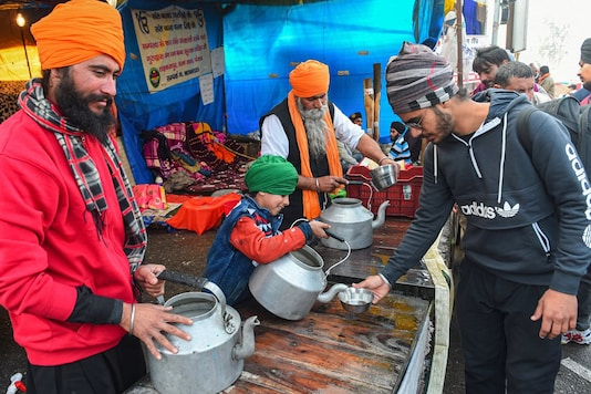 Volunteers serve water and beverages during the ongoing farmer's agitation against new farm laws, at Singhu border in New Delhi, Tuesday, January 12, 2021. (Image: PTI)