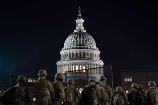 Members of the National Guard gather outside the US Capitol in Washington, DC, a day before the House of Representatives' move to impeach Donald Trump. (AFP)