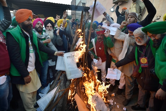 New Delhi:Farmers burn copies of the new farm laws as they celebrate Lohri festival during their ongoing protest against the central government, at Singhu border in New Delhi, Wednesday, Jan. 13, 2021. (PTI Photo/Manvender Vashist)