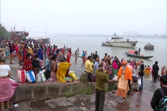 Devotees perform rituals and take holy dip in Hoogly river on the occasion of Makar Sankranti today. (Image: ANI)