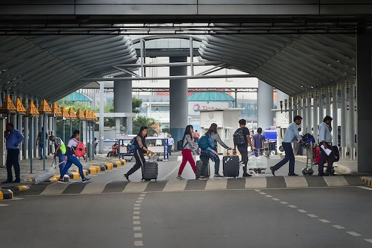 Passengers cross a road with their luggage, outside an airport in India. (Source: PTI)