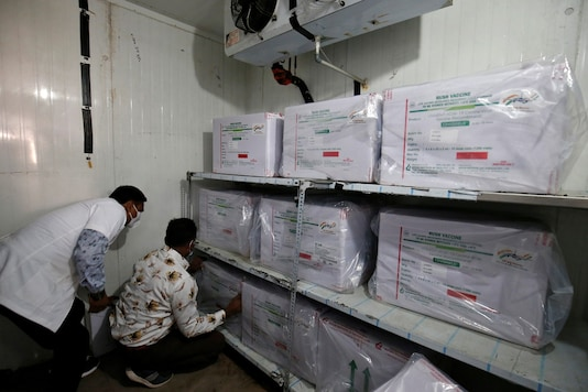Officials arrange boxes containing vials of COVISHIELD inside a cold storage room at a vaccination storage centre in Ahmedabad. (Reuters)