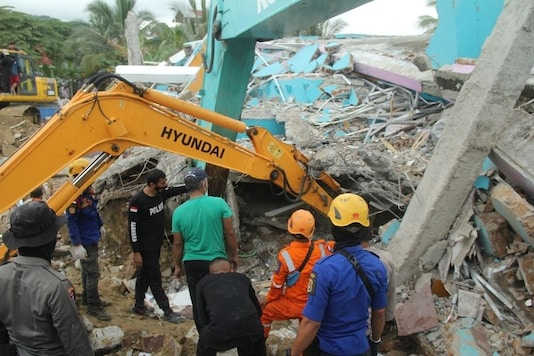 Rescuers use an excavator to dig through a damaged hospital building to search for survivors following an earthquake in Mamuju, West Sulawesi province, Indonesia, January 15, 2021 in this photo taken by Antara Foto. Antara Foto/Akbar Tado/ via REUTERS