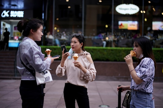 Women wearing face masks eat ice cream on a street in Shanghai, following the coronavirus disease (COVID-19) outbreak, China June 16, 2020. REUTERS/Aly Song - RC2BAH9MEQYR