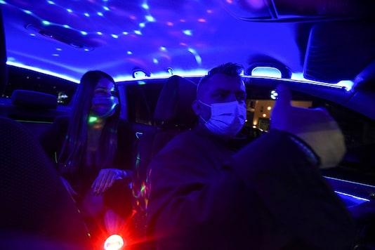 Greek driver Konstantinos Bekios, who has turned his taxi into a 'night club', gives a thumbs up to passenger Ioanna Karagiannidou, amid the coronavirus disease (COVID-19) pandemic, in Thessaloniki, Greece, January 14, 2021. REUTERS/Alexandros Avramidis