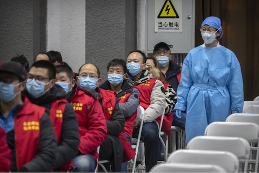 A medical worker wearing protective equipment monitors patients after they received the coronavirus vaccine at a vaccination facility in Beijing, Friday, Jan. 15, 2021. A city in northern China is building a 3,000-unit quarantine facility to deal with an anticipated overflow of patients as COVID-19 cases rise ahead of the Lunar New Year travel rush. Image Credits: AP.