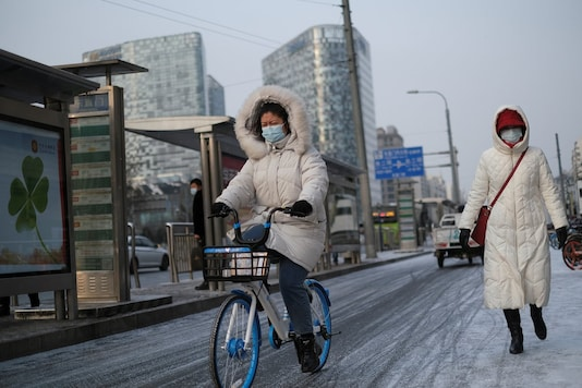 A woman wearing a face mask following the coronavirus disease (COVID-19) outbreak, rides a bicycle on the street during a snowy morning in Beijing, China, January 19, 2021. (Image: REUTERS)