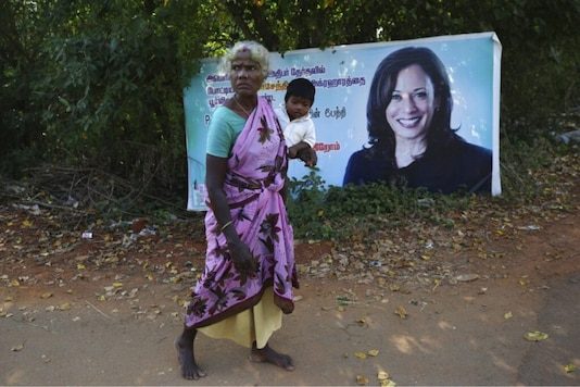An Indian village woman carries a child and walks barefoot past a banner featuring U.S. democratic vice presidential candidate Sen. Kamala Harris in Thulasendrapuram village, south of Chennai, Tamil Nadu state, India, Tuesday, Nov. 3, 2020. The lush green village is the hometown of Harris' maternal grandfather who migrated from there decades ago. (AP Photo/Aijaz Rahi)