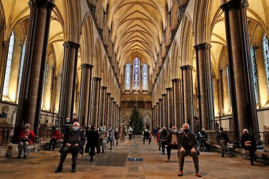 People sit and relax after receiving their Pfizer-BioNTech vaccination at Salisbury Cathedral in Salisbury, England. (AP Photo/Frank Augstein)